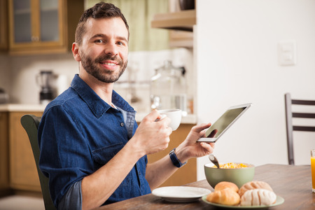 networking people: Hispanic young man using a tablet computer and smiling while enjoying a nice breakfast at home
