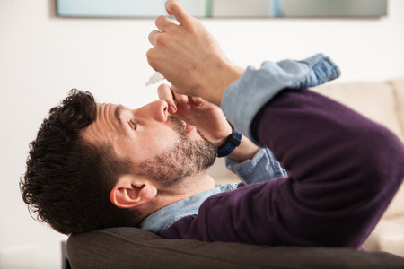 Profile view of a young man laying back on a couch and pouring some eye drops at home