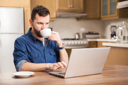 attractive male: Portrait of a young busy man with a beard drinking some coffee and using a laptop computer to work from home