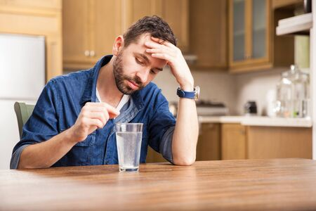 dissolve: Guy with a beard and a denim shirt waiting for an effervescent tablet to dissolve and cure his indigestion at home