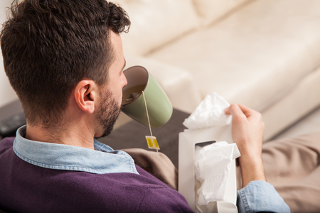 personne malade: Point de vue d'un jeune homme malade de boire un peu de th� � facilement quelques-uns des sympt�mes d'un rhume � la maison