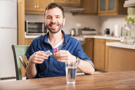 taking medicine: Handsome Hispanic young man taking some medicine with a glass of water at home and smiling
