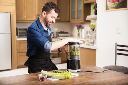 food processor: Good looking young man making a smoothie for breakfast using a blender at home