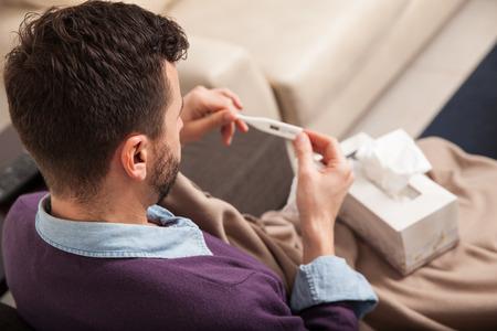 persona enferma: Punto de vista de un joven enfermo con fiebre que controla su temperatura en un term�metro Foto de archivo