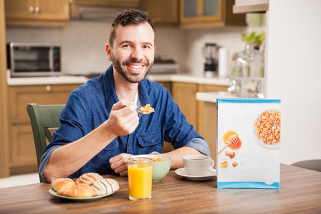 cereal box: Portrait of a good looking young man eating cereal and smiling at home. Cereal box included Stock Photo