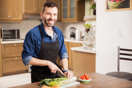 home cooking: Portrait of a Hispanic young man in an apron cutting some vegetables and making a salad at home Stock Photo
