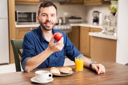 jugo de frutas: apuesto joven con una barba de comer una manzana para el desayuno en casa Foto de archivo