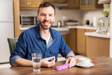 Portrait of a good looking happy Hispanic man taking his vitamins in the morning at home Stok Fotoğraf