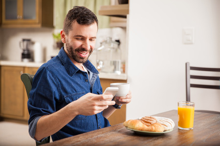 email: Attractive young man in denim shirt texting on his smartphone while having breakfast at home