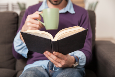 book: Closeup of a young man reading a book while drinking coffee from a mug at home Stock Photo