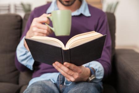 persona leyendo: Primer de un hombre joven que lee un libro mientras toma café de una taza en el hogar Foto de archivo