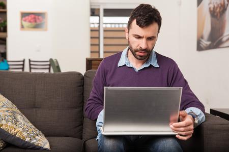 buen vivir: Hombre apuesto con una barba que trabaja en su computadora portátil mientras está sentado en un sofá en la sala de estar