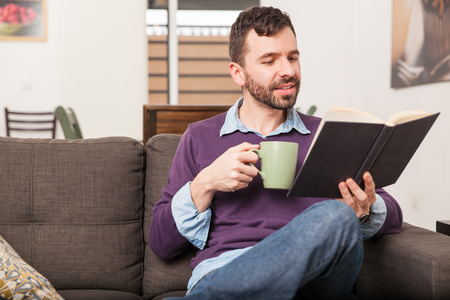 Attractive man enjoying a cup of coffee and a good read while relaxing on his couch Фото со стока
