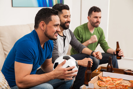 the guy: Profile view of a group of three male friends watching a soccer game on TV while drinking beer and eating pizza