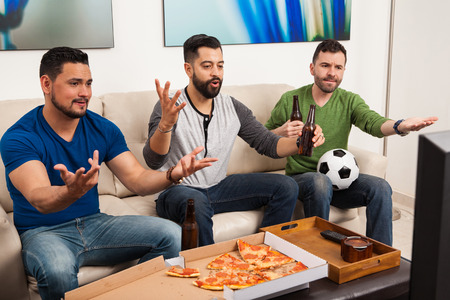 unfair: Group of three gruys watching a soccer game on TV and yelling at the screen because of an unfair play Stock Photo