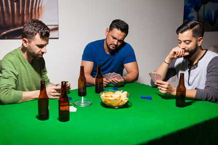 guys: Group of three male friends drinking beer and playing cards for poker night at home
