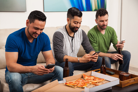 guys: Attractive young Latin men hanging out at home, drinking beer and eating pizza while using their smartphones all at the same time Stock Photo