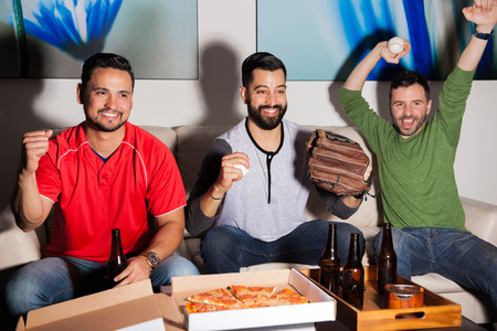 cheering fans: Group of male friends watching a baseball and celebrating a home run from their favorite team Stock Photo