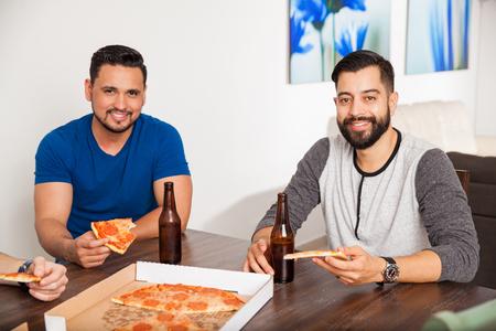 hombre tomando cerveza: Retrato de un par de chicos comiendo pizza y bebiendo cerveza en el país