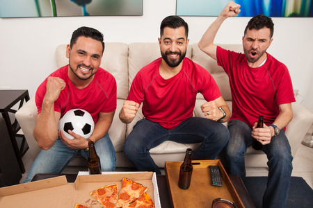 football fans: Wide angle portrait of three male friends and soccer fans celebrating a goal and a victory while watching the game on TV Stock Photo