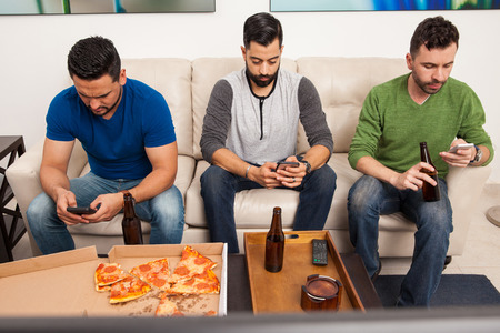 media room: Portrait of a group of three men hanging out but ignoring each other while using their smartphones