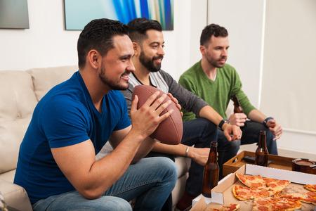 ピザを食べるといくつかのビールを飲みながらテレビでアメリカン フットボールの試合を見ている男の束のプロファイル表示 写真素材