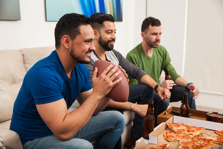 fans: Profile view of a bunch of guys watching an american football game on TV while eating pizza and drinking some beer