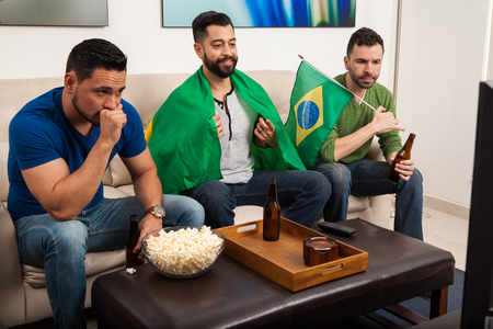 expectations: Three young men watching the Brazil sports competitions on TV at home and drinking some beer