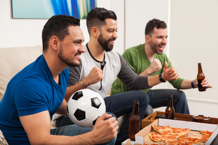 Three young Latin men celebrating a goal while watching a soccer game at home with pizza and beer
