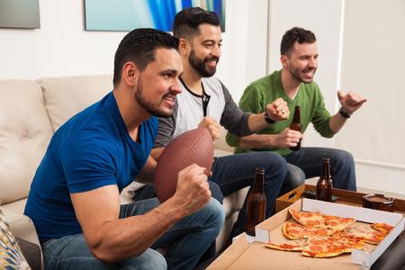 personas festejando: Vista de perfil de un grupo de amigos varones animando a su equipo de fútbol viendo el partido en casa