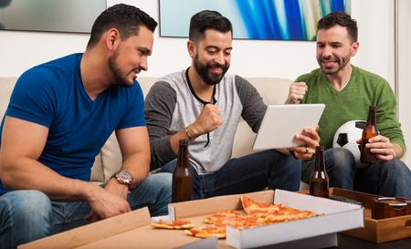 Mannelijke vrienden drinken van bier en het eten van pizza tijdens het kijken naar een voetbalwedstrijd op een tablet-computer
