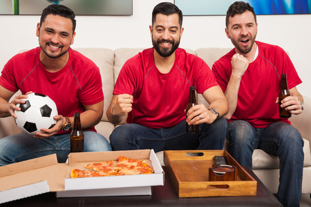 jerseys: Group of three male friends wearing their favorite soccer team jerseys and watching a game with pizza and beer Stock Photo