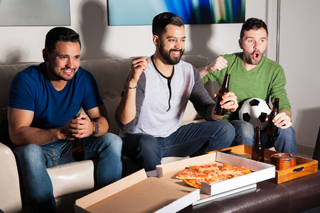 Group of three guys with a beard watching a soccer game on TV and celebrating a goal while hanging out at home