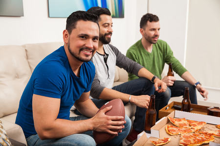 watching football: Portrait of a young Handsome Hispanic man watching an american football game with his friends and eating some pizza Stock Photo