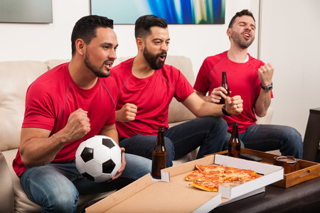 rooting: Three Hispanic male friends rooting for their soccer team on TV and celebrating a goal Stock Photo