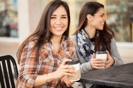 hispanic woman: Portrait of a gorgeous Hispanic young woman hanging out with her friends and enjoying a cup of coffee