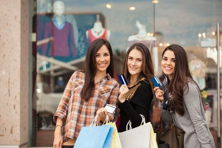 Tres chicas jóvenes latinos gastar algo de dinero en un centro comercial y que muestran sus tarjetas de crédito. Espacio de copia extra.