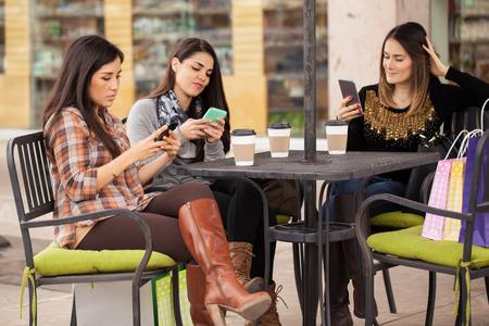 Groep van drie jonge vrouwen met behulp van hun eigen smartphone en het negeren van elkaar onder het genot van koffie buitenshuis