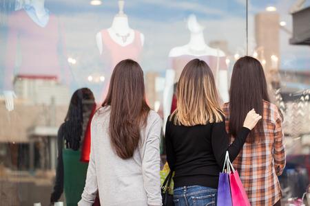 衣料品店のディスプレイを見ている 3 人の女性のグループの後姿