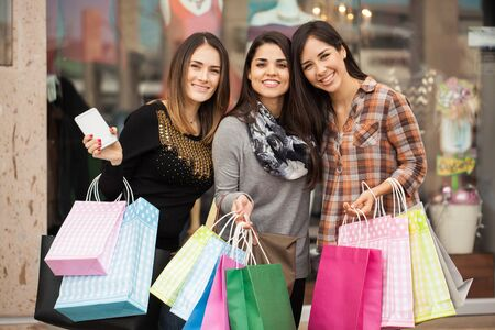 Portrait of a group of three Hispanic girlfriends carrying a lot of shopping bags outside of a clothing store