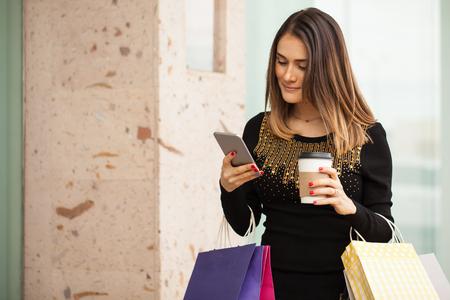 donna ricca: Bella bruna con il suo smartphone e bere il caffè mentre si fa shopping in un centro commerciale