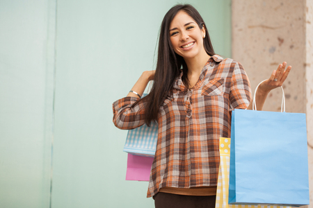 hispanic woman: Happy young Hispanic woman carrying some shopping bags and buying stuff at a mall