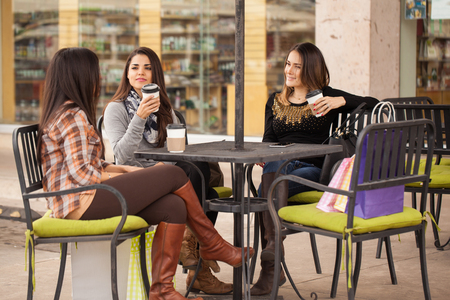 women coffee: Group of cute young women sitting in a restaurant and drinking coffee after a day of shopping