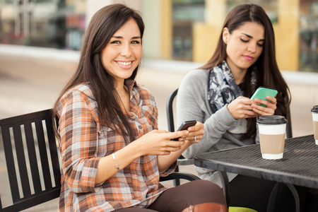 hispanic girls: Cute young Hispanic brunette using her smartphone and smiling while having coffee with some friends