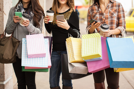 women coffee: Closeup of a group of three young and rich women carrying a lot of shopping bags and a cup of coffee and smartphone each