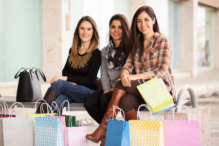 Portrait of a group of three friends taking a break after a shopping spree at the mall