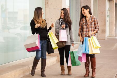 happy smiling: Full length portrait of a group of rich women walking around a mall with a lot of shopping bags Stock Photo