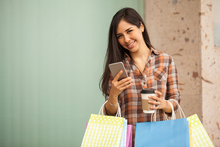 Cute Hispanic young woman carrying many shopping bags and texting on her smartphone Zdjęcie Seryjne