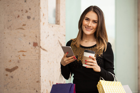 contact center: Gorgeous young woman carrying many shopping bags while using her smartphone and drinking some coffee in a mall Stock Photo