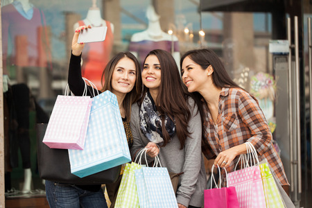 Group of cute female friends doing some shopping at a mall and taking a selfie with a smartphone 스톡 콘텐츠